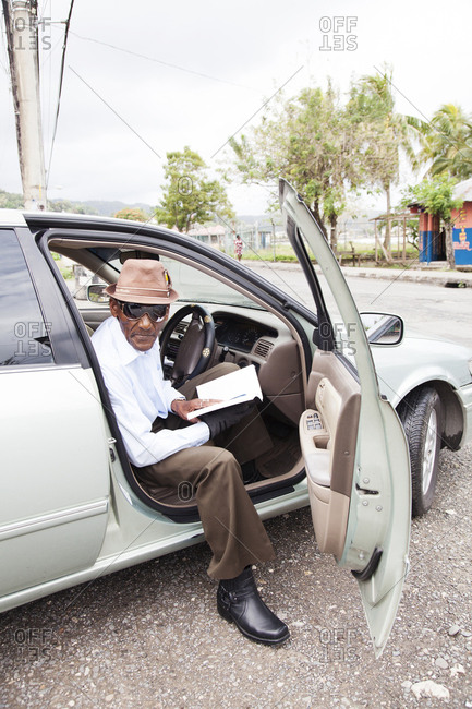January 31, 2012: JAMAICA, Port Antonio. Albert Minnot, singer of the mento band, The Jolly Boys, sitting in his car.
