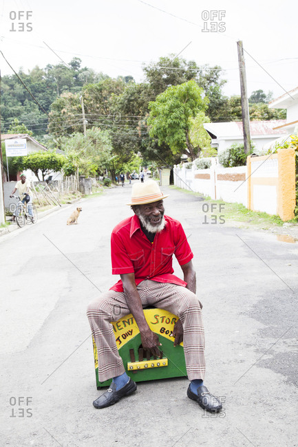 "January 31, 2012: JAMAICA, Port Antonio. Derrick ""Johnny"" Henry of the Mento band, The Jolly Boys, sitting and playing the marimba box."
