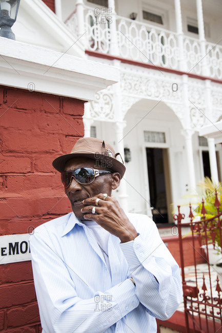 January 31, 2012: JAMAICA, Port Antonio. Albert Minott, lead singer of the Jolly Boys standing in front of a historical building.