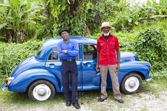 """January 31, 2012: JAMAICA, Port Antonio. Joseph """"Powder"""" Bennett and Derrick """"Johnny"""" Henry of the Mento band, The Jolly Boys standing in front of a vintage blue car."""