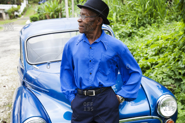 "January 31, 2012: JAMAICA, Port Antonio. Joseph ""Powder"" Bennett of the Mento band, The Jolly Boys standing in front of a vintage blue car."