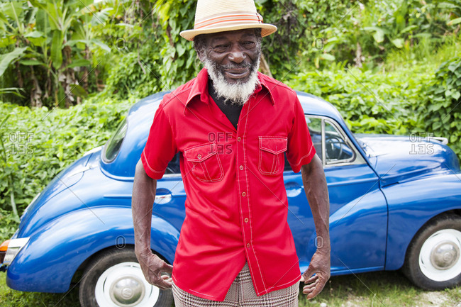 "January 31, 2012: JAMAICA, Port Antonio. Derrick ""Johnny"" Henry of the Mento band, The Jolly Boys standing by a blue vintage car."