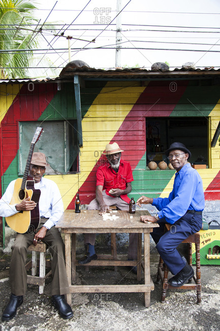 "January 31, 2012: JAMAICA, Port Antonio. Albert Minott, Joseph ""Powder"" Bennett and Derrick ""Johnny"" Henry of the Mento band, The Jolly Boys playing dominoes at the Willow Wind Bar."