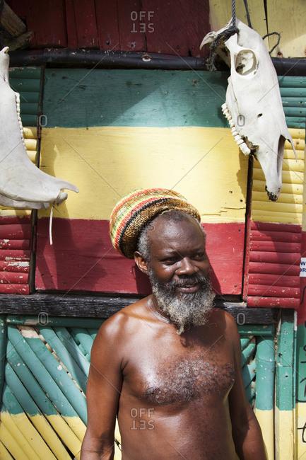 February 1, 2012: JAMAICA, Port Antonio. A rastafari and his beach shack at the Winnifred Beach.