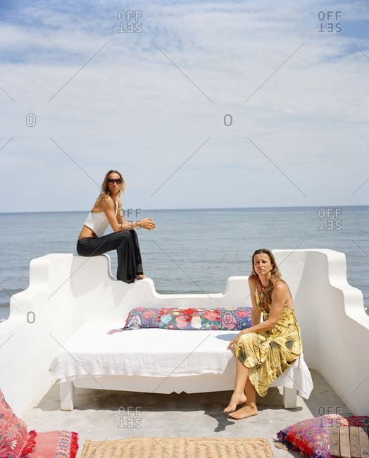 January 13, 2010: MEXICO, Sayulita, two young women relaxing on terrace with sea in background, portrait