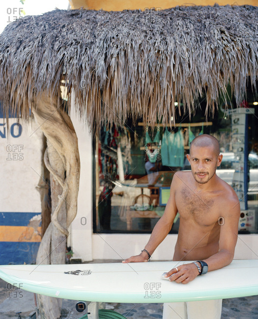 January 13, 2010: MEXICO, Sayulita, Young surfer cleaning his surfboard in front of a surf store.