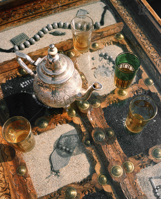 January 14, 2010: OMAN, Muscat, Barr Al Jissah Resort and Spa, silver teapot and glass tea cups on a table, close-up