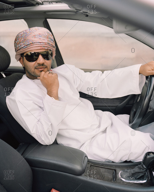 January 14, 2010: OMAN, Muscat, young man in traditional clothing sitting in his car
