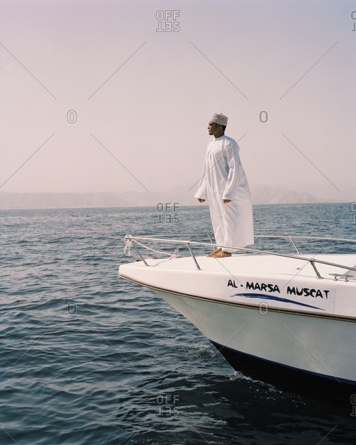 January 14, 2010: OMAN, Muscat, man standing on deck of boat in traditional clothing at sea