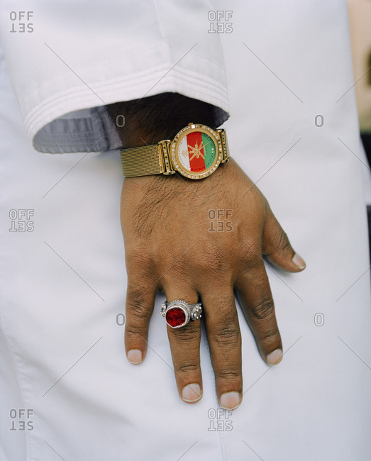 January 14, 2010: OMAN, Muscat, man wearing wristwatch and finger ring, Omani flag designed on watch dial