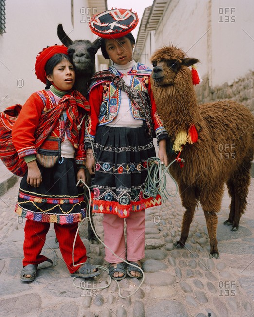 October 5, 2010: PERU, Cusco, South America, Latin America, girls wearing traditional clothing standing with Llama in a street in Cusco.