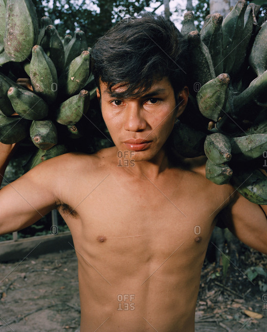 October 5, 2010: PERU, Amazon Rainforest, South America, Latin America, portrait of a young man carrying bananas