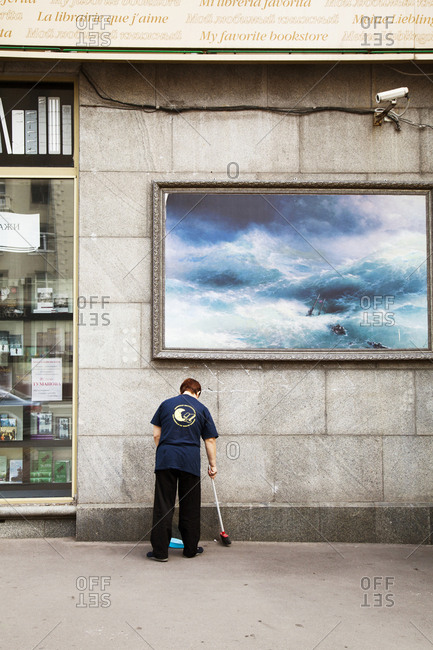July 3, 2011: RUSSIA, Moscow. A woman sweeping in front of a painting on Tverskaya Street.