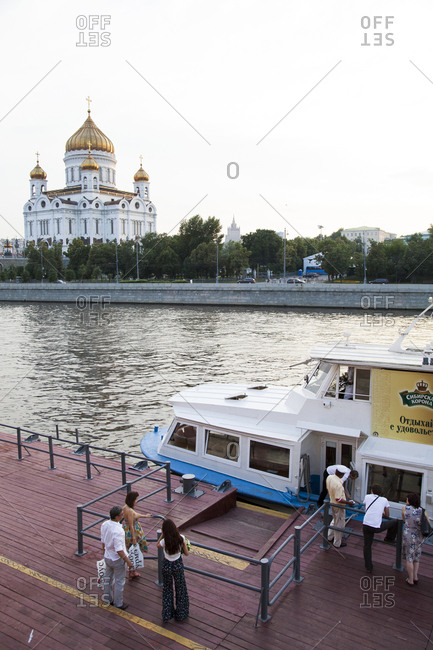 July 3, 2011: RUSSIA, Moscow. People waiting at a Moscow River Ferry Dock with the Cathedral of Christ the Savior in the background.