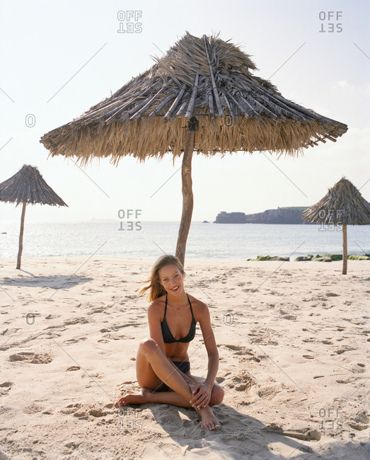April 13, 2017: SPAIN, Andalusia, Tarifa, young woman in bikini top relaxing on sand at beach, portrait