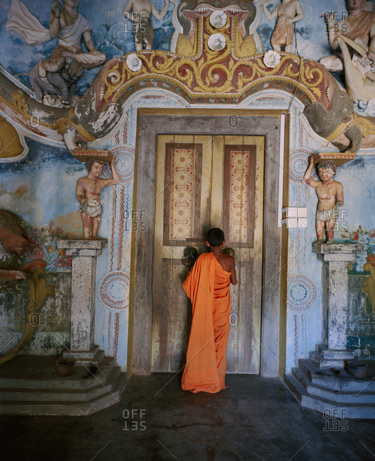 April 13, 2017: SRI LANKA, Asia, rear view of a monk standing in front of temple's door