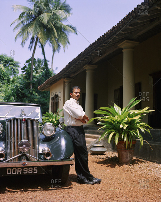 April 13, 2017: SRI LANKA, Asia, Galle,  portrait of a driver standing by vintage car in front of the Dutch House Hotel.