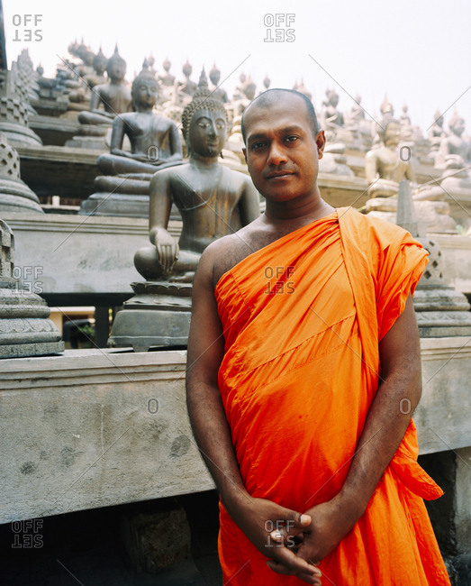 April 13, 2017: SRI LANKA, Asia, portrait of a monk with Buddha statues in the background