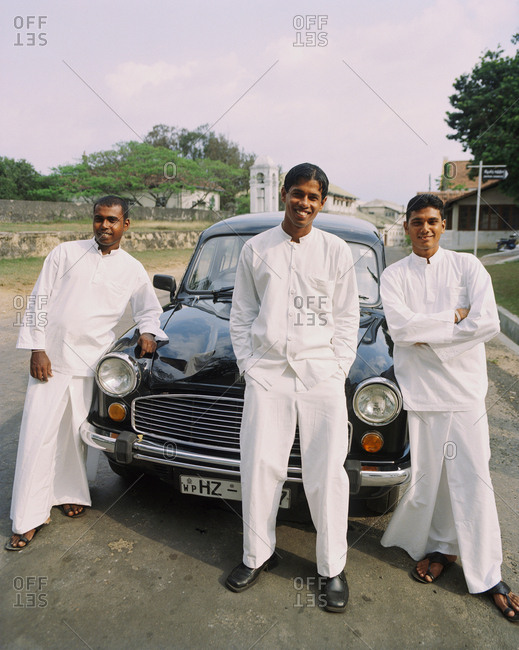 April 13, 2017: SRI LANKA, Asia, Galle, portrait of Bell Hop and Concierge of the Amangalla Hotel standing in front of Vintage car