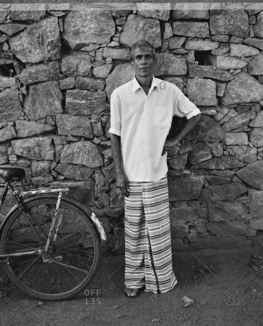 April 13, 2017: SRI LANKA, Asia, portrait of man standing by stone wall (B&W)