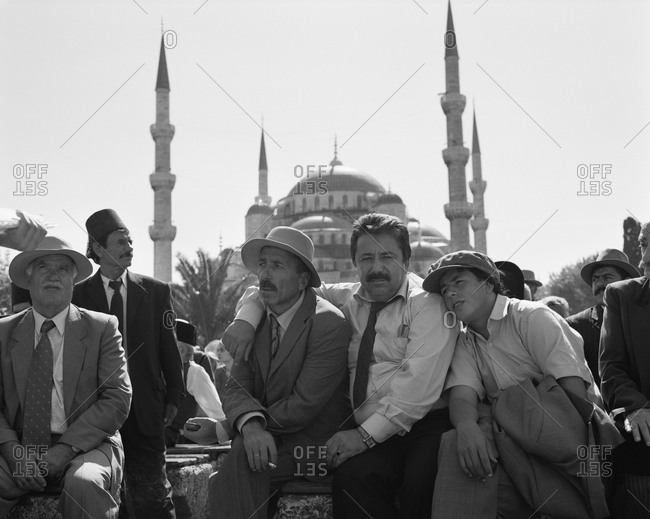 August 12, 2010: TURKEY, Istanbul, actors sitting together with mosque in the background (B&W)