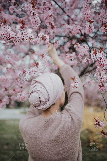 Woman holds branch of cherry blossoms