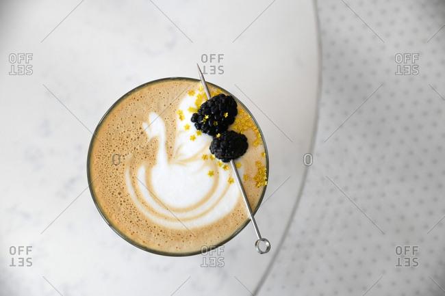 Latte served with blackberries