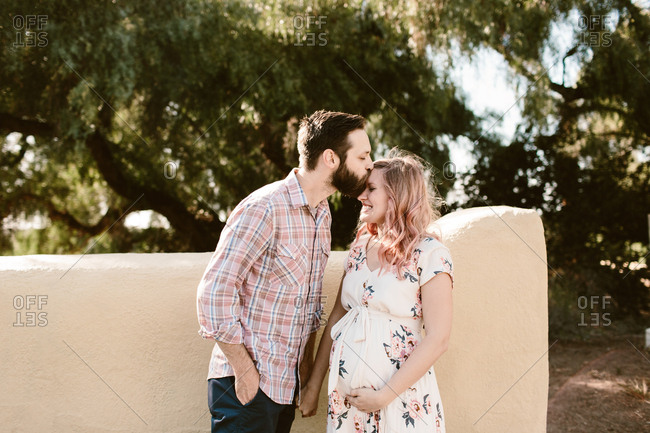Maternity photo of pregnant woman with husband kissing her forehead