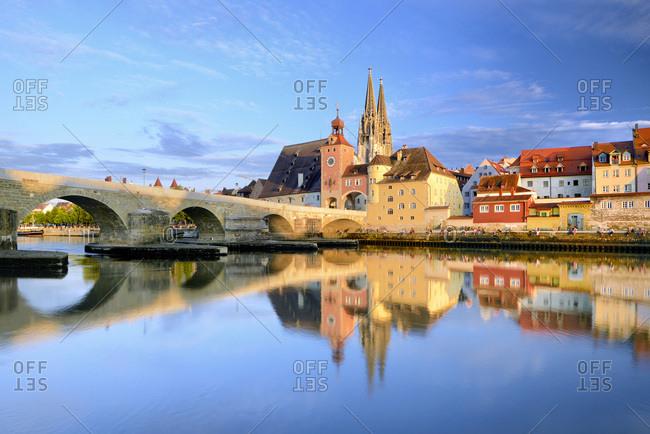 July 11, 2017: Germany, Bavaria, Bayern, Upper Palatinate, Oberpfalz, Regensburg, Regensburg Cathedral, Danube, Donau, Danube, The Stone Bridge, St. Peter Church and the Old Town of Regensburg reflecting on the Danube river