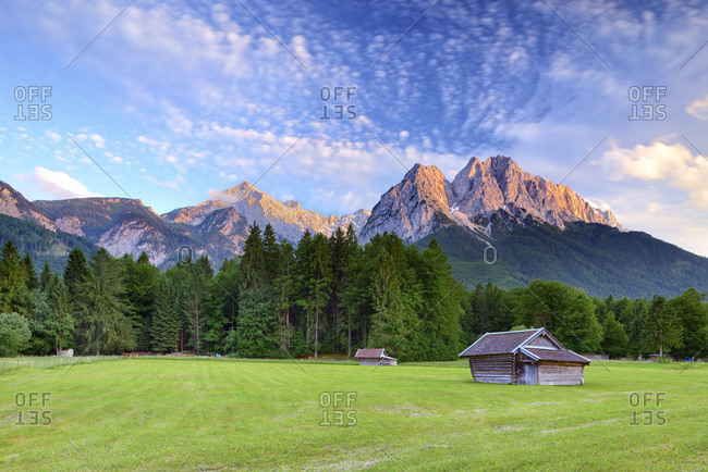 Germany, Bavaria, Bayern, Upper Bavaria, Oberbayern, Garmisch-Partenkirchen, Typical Bavarian landscape with German alps with wooden huts on grass field