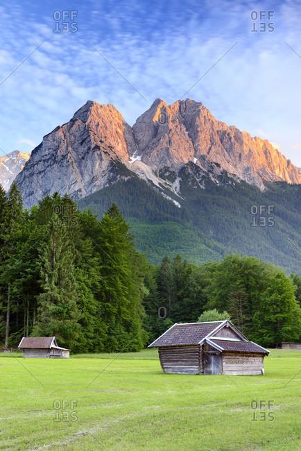 Germany, Bavaria, Bayern, Upper Bavaria, Oberbayern, Garmisch-Partenkirchen, Typical Bavarian landscape with German alps with wooden huts on grass field