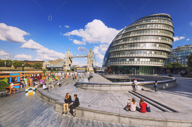 August 15, 2017: United Kingdom, England, London, City of London, Tower Bridge, Great Britain, tourists enjoying the sun with Tower Bridge and the Town Hall in the background