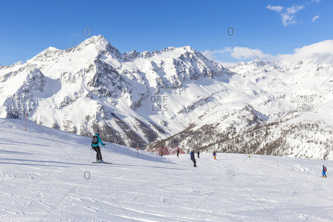 January 23, 2018: Italy, Aosta Valley, Aosta district, Alps, Monterosa Ski, Skiers on the ski slopes at alpe Mandria and Breithorn in Monte Rosa Massif in Background, Frachey near Champoluc