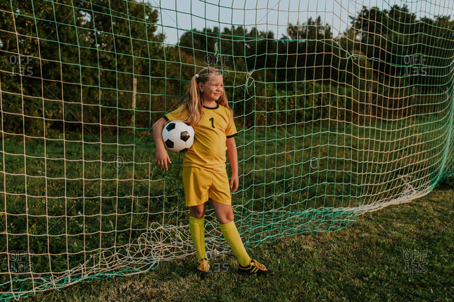 Girl goalkeeper with ball standing at goal on soccer field.