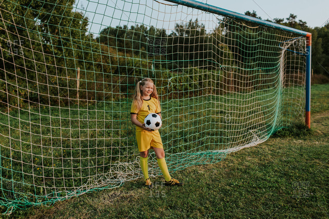 Full length of young teenage girl in yellow soccer dress holding ball in front of soccer net.