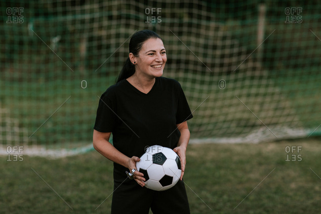 Cheerful female football referee standing at goal on football field.