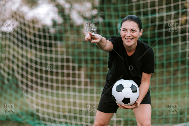 Amateur woman referee in black soccer dress holding ball in front of soccer net.