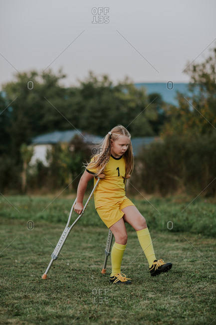 Girl with crutches walking along football field.