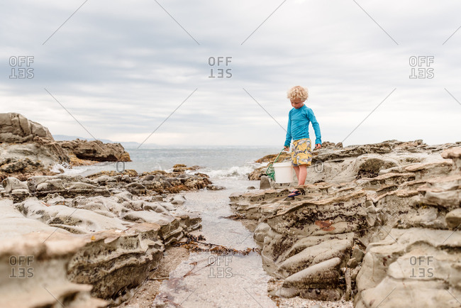 Young boy carrying bucket and net by the ocean