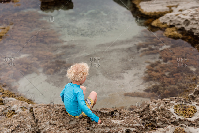 Boy sits by tide pool
