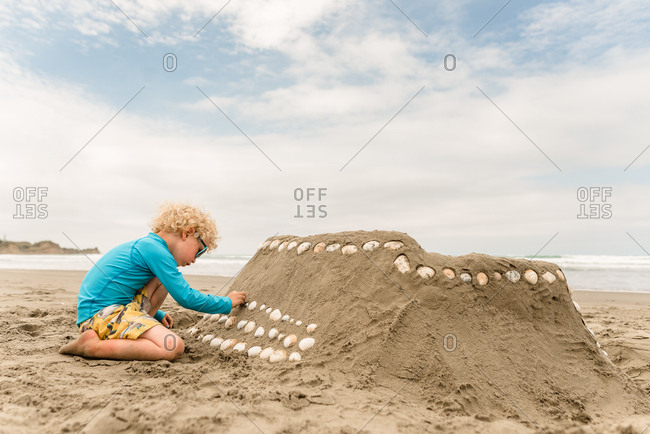 Young boy decorating a sand castle with shells