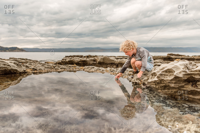 Inquisitive boy dredging a tide pool by the bay