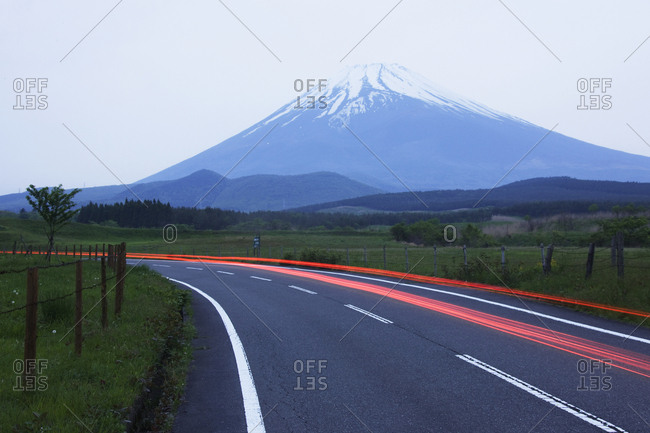 Blurred headlights on road before mountain, Japan