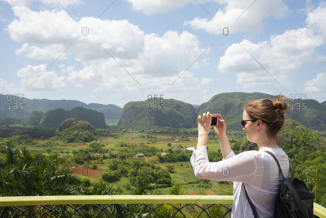 Woman photographing the valley of Vinales, Cuba.