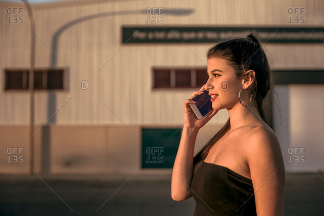 Nice brunette girl talking on the phone on the street during the sunset