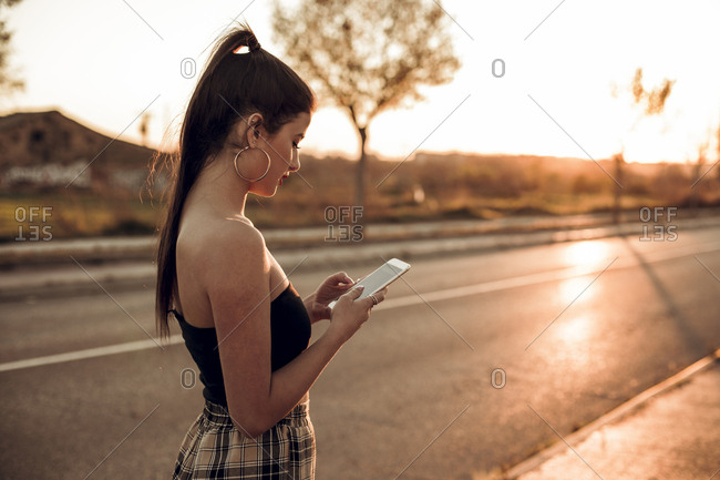 Pretty brunette girl texting on her mobile phone on the street during the sunset