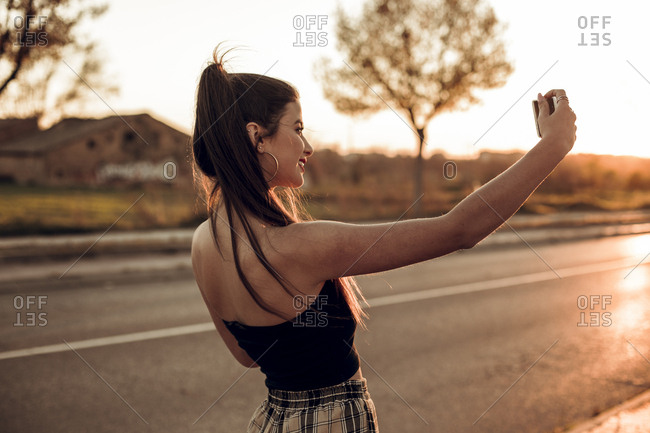 Beautiful brunette girl taking a selfie with her mobile phone on the street during sunset