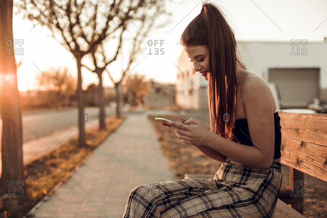 Pretty brunette girl sitting on a bench during the sunset