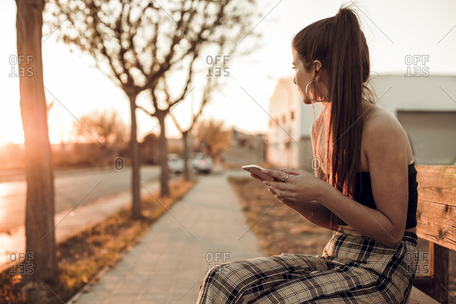Pretty brunette girl on a bench during the sunset