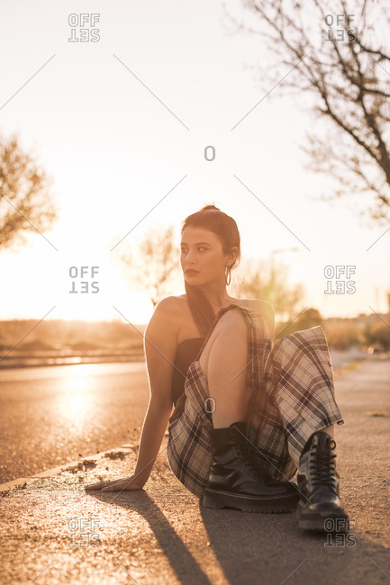 Portrait of a pretty brunette girl on the street during sunset